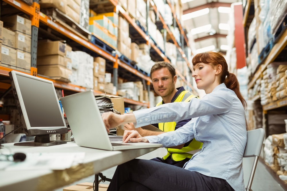 Warehouse worker and manager looking at laptop in a large warehouse.jpeg